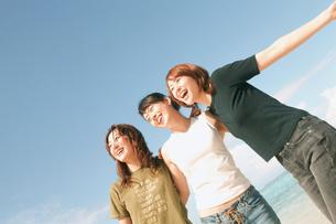 空と肩を組む女性3人の写真素材 [FYI02065597]