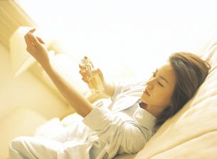 横になり手にコロンをつける女性の写真素材 [FYI02065598]