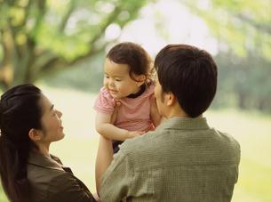 公園で抱っこする家族の写真素材 [FYI02065602]