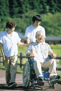 車椅子に座るシニア男性と婦人と息子の写真素材 [FYI02065787]