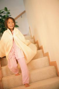 タオルを肩にかけて階段を下りる女の子の写真素材 [FYI02065790]