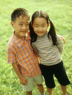 草原に並ぶ男の子と女の子の写真素材 [FYI02065794]