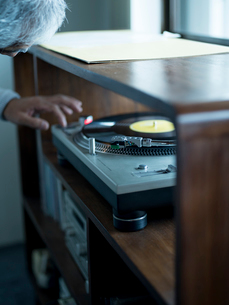 レコードプレイヤーを操作するシニア男性の写真素材 [FYI02065816]
