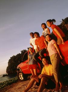 浜辺に止めた赤い車と若者7人の写真素材 [FYI02065821]