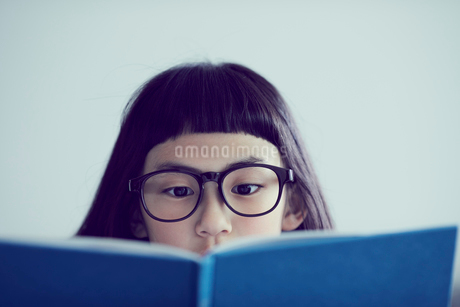 本を読むメガネをかけた女の子の写真素材 [FYI02065852]