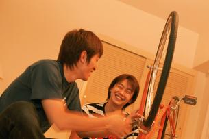 室内で自転車を整備する男性2人の写真素材 [FYI02065861]