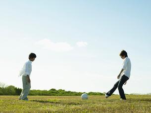 公園でサッカーの練習をする男の子とお父さんの写真素材 [FYI02065919]
