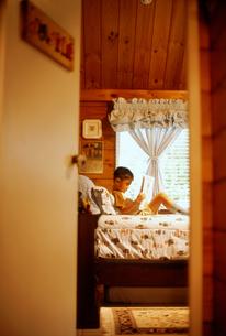 ベッドで本を読む男の子の写真素材 [FYI02065948]