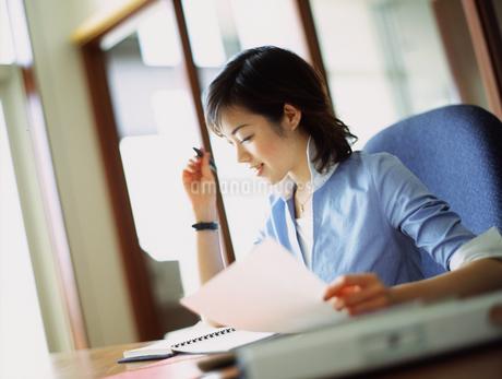 書類を手にとる女性の写真素材 [FYI02066004]