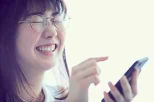 スマートフォンを操作するメガネをかけた女性の写真素材 [FYI02066063]