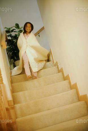 タオルを肩にかけて階段を下りる女の子の写真素材 [FYI02066064]