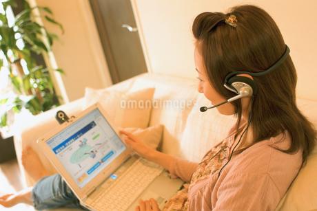 ソファでノートパソコンを開く女性の写真素材 [FYI02066202]