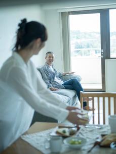 食事の準備をする女性とソファでくつろぐ男性の写真素材 [FYI02066231]
