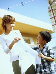 洗濯物を干す母親と男の子の写真素材 [FYI02066347]