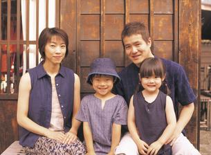 軒先のベンチに座る家族4人の写真素材 [FYI02066349]