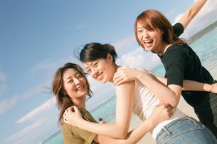 浜辺で肩を組む女性3人の写真素材 [FYI02066399]