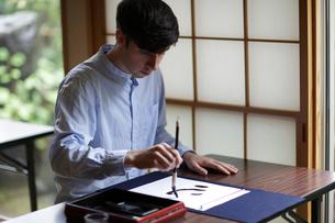 書道をする外国人男性の写真素材 [FYI02066469]