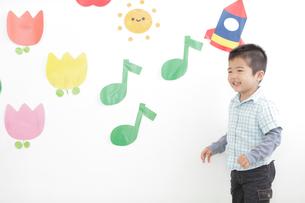 壁に貼ったイラストと笑顔の男の子のイラスト素材 [FYI02066501]