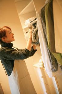 セーターを棚にしまう女性の写真素材 [FYI02066531]