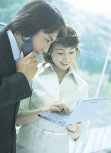 電話とビジネスマンとパソコンを持つビジネスウーマンの写真素材 [FYI02066544]