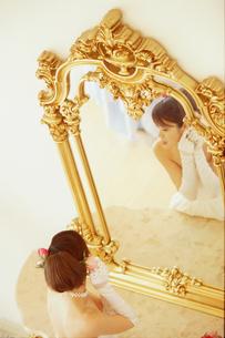 鏡の前のウェディングドレスの女性の写真素材 [FYI02066551]