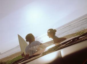 浜辺に止めた車の前のカップルの写真素材 [FYI02066585]