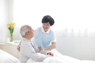 ベッドに座るシニア男性と男性介護士の写真素材 [FYI02066639]