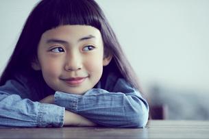 机に伏せる微笑む女の子の写真素材 [FYI02066694]