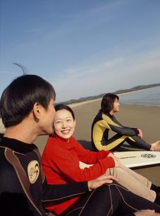 砂浜に座るサーファー3人の写真素材 [FYI02066699]
