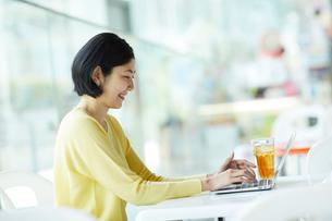 カフェでノートパソコンを操作する女性の写真素材 [FYI02066700]