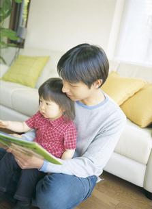 父親に本を読んでもらう女の子の写真素材 [FYI02066707]