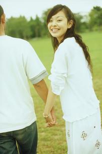 草原で手を繋ぐカップル後姿の写真素材 [FYI02066717]