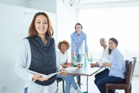笑顔の日本人女性とミーティングをする同僚たちの写真素材 [FYI02066719]