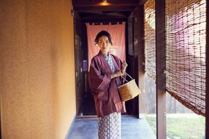 温泉の入り口に立つ浴衣姿のミドル女性の写真素材 [FYI02066797]