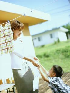 洗濯物を干す母親と男の子の写真素材 [FYI02066814]