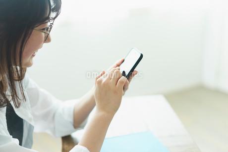 スマートフォンを操作するメガネをかけた女性の写真素材 [FYI02066843]