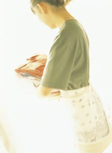 たたんだ衣類を運ぶ女性の写真素材 [FYI02066854]
