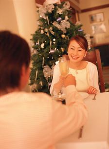 クリスマスツリーのあるレストランで乾杯するカップルの写真素材 [FYI02066857]
