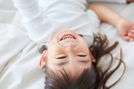 寝転ぶ笑顔の女の子の写真素材 [FYI02066865]