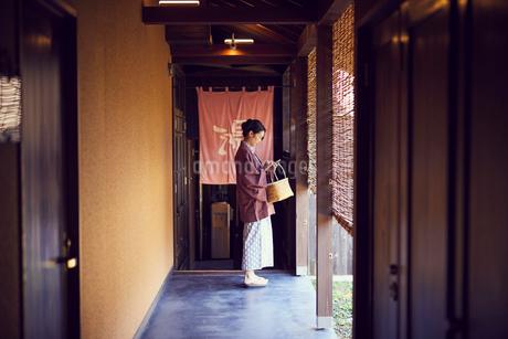 温泉の入り口に立つ浴衣姿のミドル女性の写真素材 [FYI02066883]