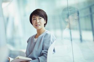 本を持ち窓の外を眺める女性の写真素材 [FYI02066936]