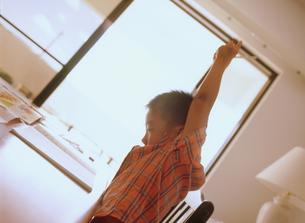 座って伸びをする男の子の写真素材 [FYI02066952]