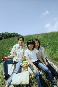 草原でピクニックする家族3人の写真素材 [FYI02066996]