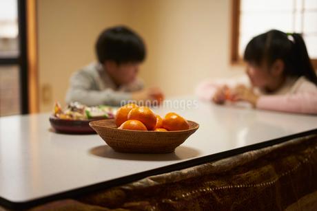 こたつの上のミカンと子供2人の写真素材 [FYI02067056]