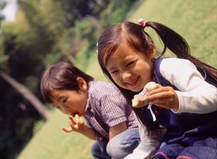 公園でドーナツを食べる子供2人の写真素材 [FYI02067078]