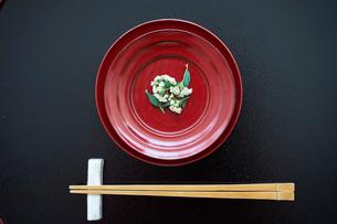 花をのせた赤い皿と箸の写真素材 [FYI02067118]