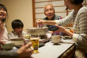 こたつで食事をする家族の写真素材 [FYI02067150]