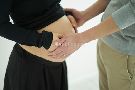 お腹に触れる妊婦と夫の写真素材 [FYI02067217]