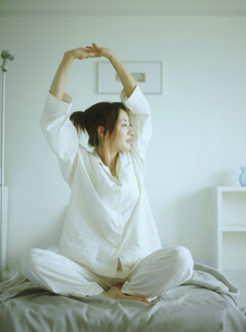 ベッドの上で伸びをするパジャマ姿の女性の写真素材 [FYI02067309]