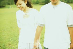 草原で手を繋ぐカップルの写真素材 [FYI02067341]